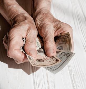 Mãos mostrando dinheiro alta vista