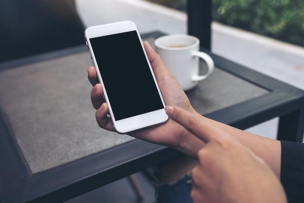 Mãos, mostrando, e, apontar, um, branca, telefone móvel, com, em branco, desktop preto, tela, em, café