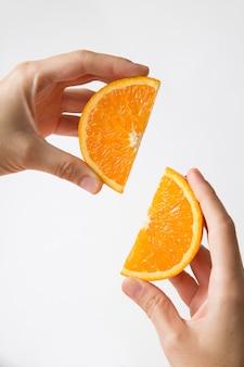 Mãos mostrando par de seções laranja suculentas cortadas