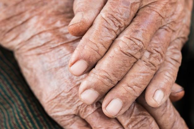 Mãos mulher idosa asiática agarra sua mão no colo