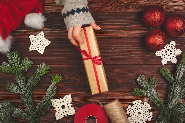 Mãos na camisola segurando um presente na mesa de madeira com decorações de natal