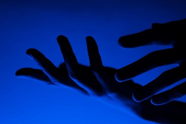 Mãos na luz de néon de contraste azul monocromático. homem mostrando sinal de gesto de palma de mão. fotografia artística.