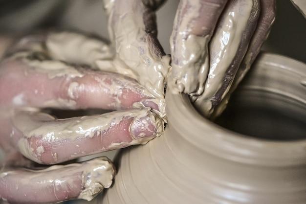 Mãos na macro de argila. fazendo crock close-up molhado bruto. mãos de homem fazendo macro de jarro de barro. o escultor na oficina faz uma jarra com um close de faiança. vaso de argila branca crua úmida closeup,