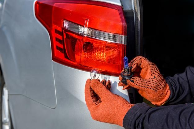 Mãos nas luvas com lâmpadas perto dos faróis dos carros