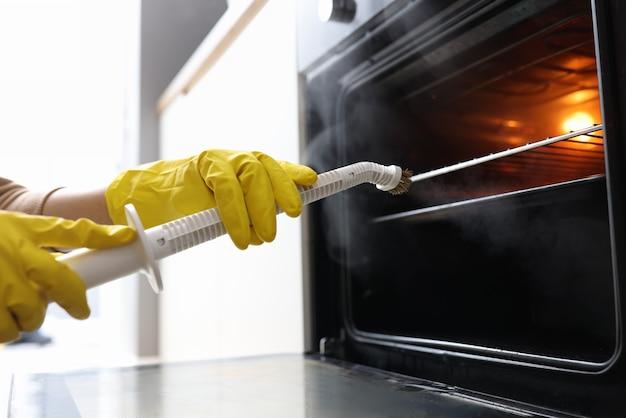 Mãos nas luvas de borracha, lavando o forno com o conceito de vaporizador. conceito de limpeza de apartamento