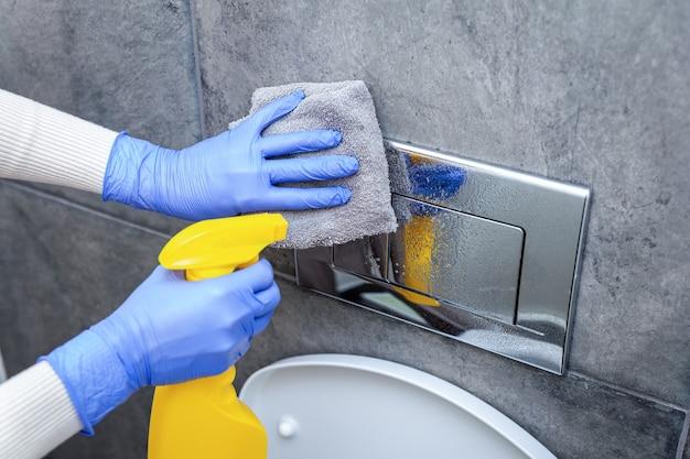 Mãos nas luvas de proteção para limpar o botão de descarga do banheiro