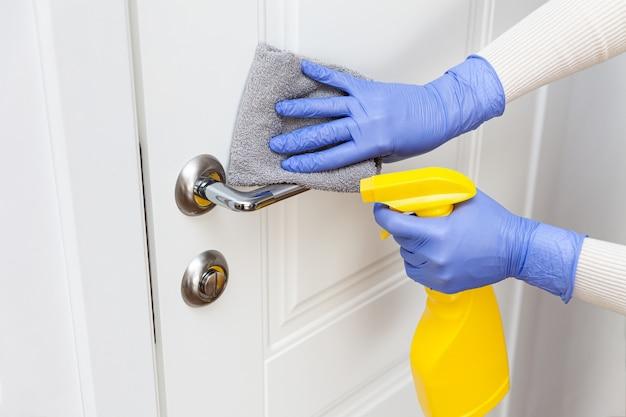 Mãos nas luvas, desinfetando a maçaneta da porta com pano e detergente em spray