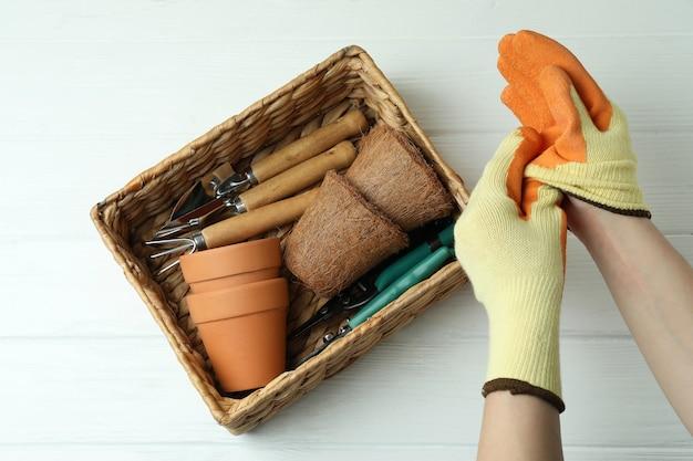 Mãos nas luvas e cesta com ferramentas de jardinagem, vista superior
