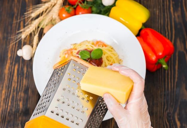 Mãos nas luvas esfregam queijo em um ralador