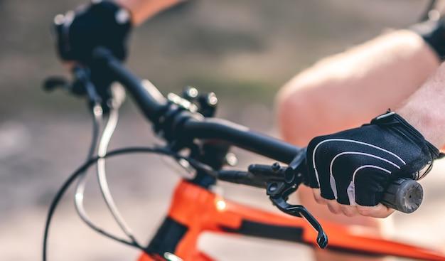 Mãos nas luvas esportivas no guidão da bicicleta durante o passeio ao ar livre