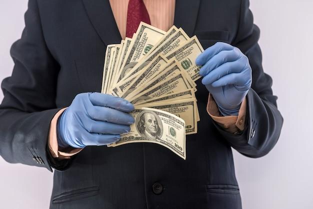 Mãos nas luvas médicas segurando a pilha de dólares para segurança, epidemia de dinheiro sujo. tudo pela saúde