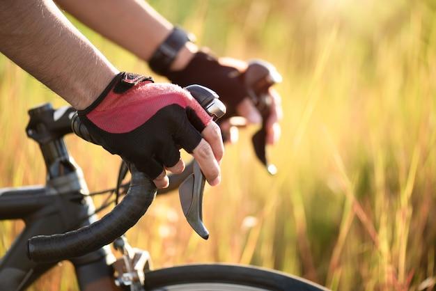 Mãos nas luvas que seguram o guiador da bicicleta da estrada. esportes e conceito ao ar livre.