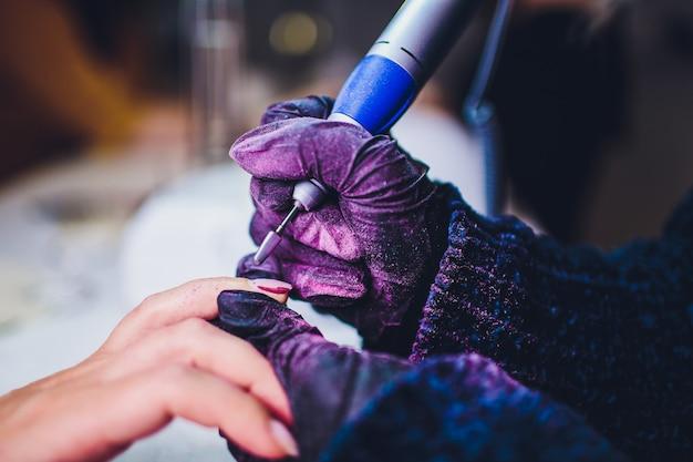 Mãos nas luvas se preocupa com as unhas do homem. manicure salão de beleza.