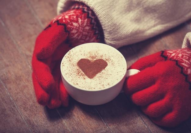 Mãos nas luvas segurando uma xícara de café quente