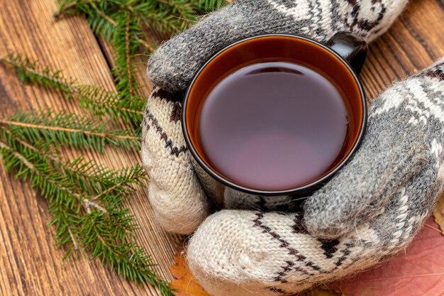 Mãos nas luvas segurando uma xícara de chá fechem na pele, fundo de ramos de pinheiro