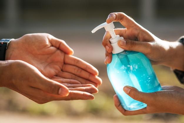 Mãos no frasco de gel para lavar as mãos e apertar para que outras pessoas lavem as mãos.