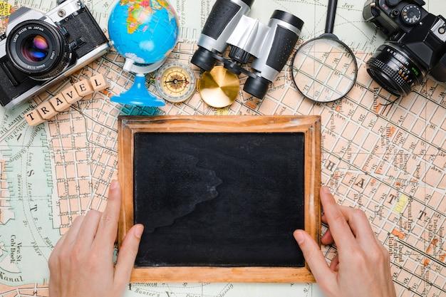 Mãos no quadro-negro rodeado por elementos de viagem