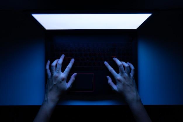 Mãos no teclado do laptop à noite.