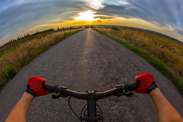 Mãos no volante andando de ciclista na estrada em direção ao pôr do sol