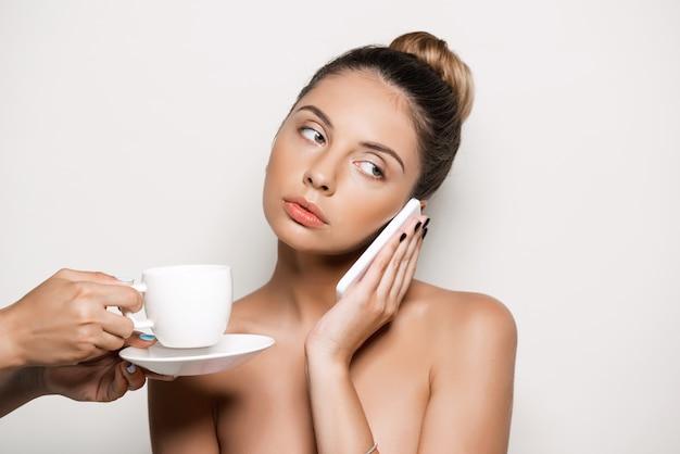 Mãos oferecendo café para mulher falando no telefone
