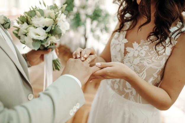 Mãos omãos de recém-casados com anéis de casamento e um buquê de casamento. recém-casados com anéis de casamento e um buquê de casamento.