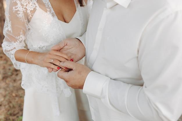 Mãos omãos de recém-casados com anéis de casamento e um buquê de casamento.