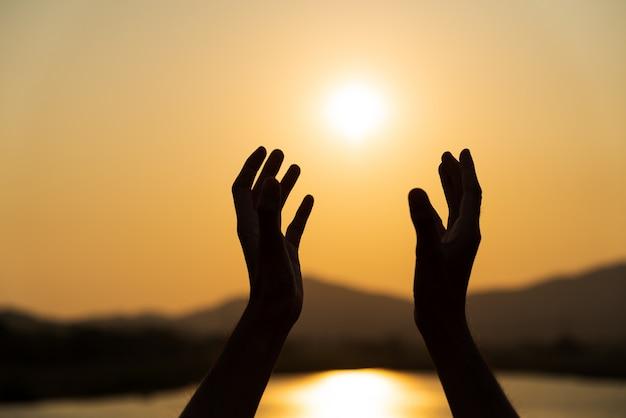 Mãos orando por bênção de deus durante o fundo por do sol. conceito de esperança.