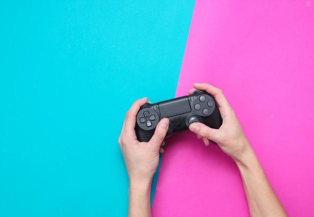 Mãos para usar o gamepad na mesa azul rosa. vista superior, minimalismo