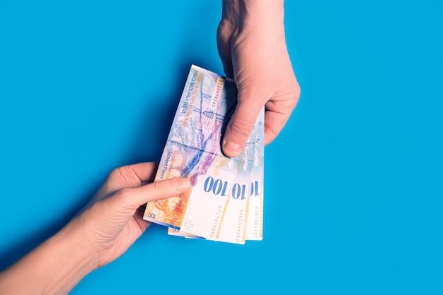 Mãos passando dinheiro, moeda suíça sobre fundo azul