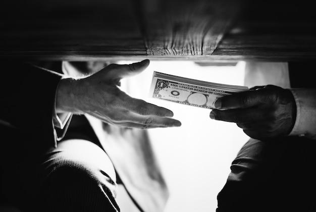 Mãos passando dinheiro por baixo da mesa, corrupção e suborno