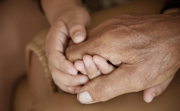 Mãos, pequeno, crianças asiáticas, segurando, pobre, idoso, avô, mãos