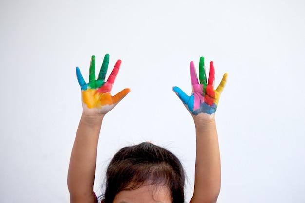 Mãos pintadas de menina pequena na pintura colorida no fundo branco