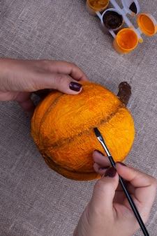 Mãos pintam uma abóbora de papel machê caseira em laranja em uma superfície de estopa
