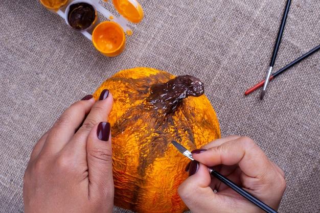 Mãos pintam uma abóbora de papel machê caseira em laranja para um feriado de outono, um hobby para crianças