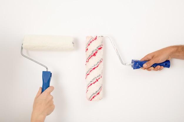 Mãos pintando a parede branca, espalhando os rolos de tinta em diferentes lados, remodelando o conceito