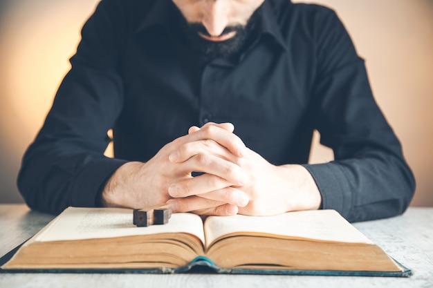 Mãos postas em oração sobre uma bíblia sagrada na igreja