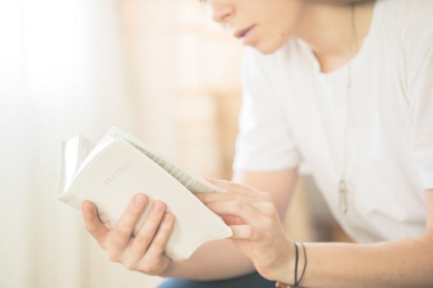 Mãos postas em oração sobre uma bíblia sagrada no conceito de igreja para a fé, espiritualidade e religião, mulher lendo a bíblia sagrada pela manhã.