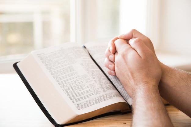 Mãos postas em oração sobre uma bíblia sagrada no conceito de igreja para fé, espiritualidade e religião