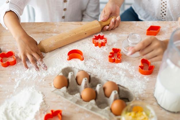 Mãos preparando biscoitos com rolo de cozinha
