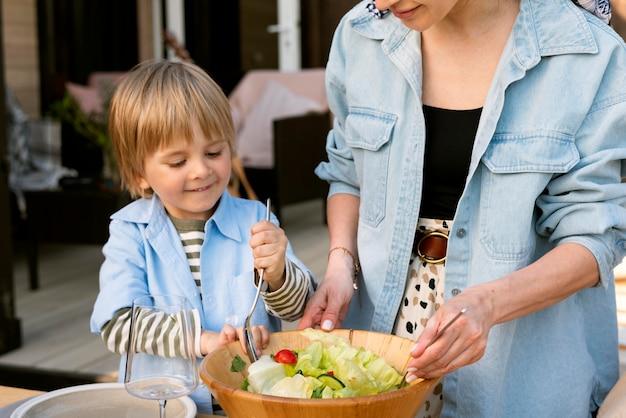 Mãos preparando salada de perto
