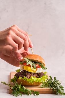 Mãos preparando um grande hambúrguer