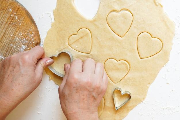 Mãos pressionando o cortador de biscoitos em forma de coração na massa