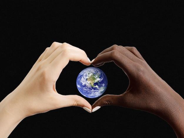 Mãos pretas e brancas em forma de coração com o planeta terra. os elementos desta imagem são cortesia da nasa. conceito de conservação da terra. amizade inter-racial impede o conceito de racismo