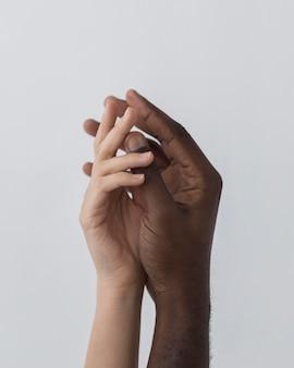 Mãos pretas e brancas se tocando