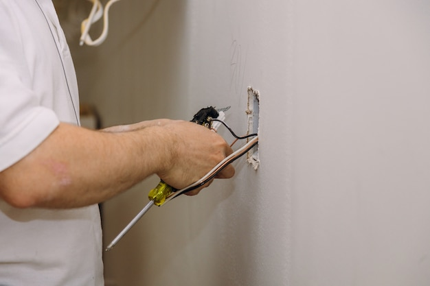 Mãos profissionais na instalação de tomadas elétricas.