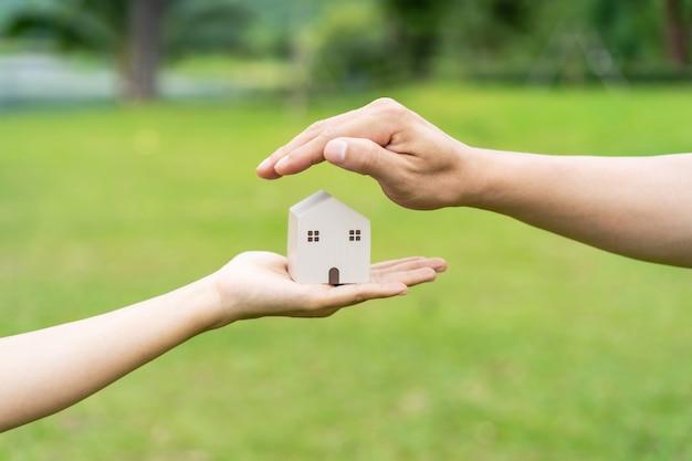 Mãos protegendo modelo de casa de madeira