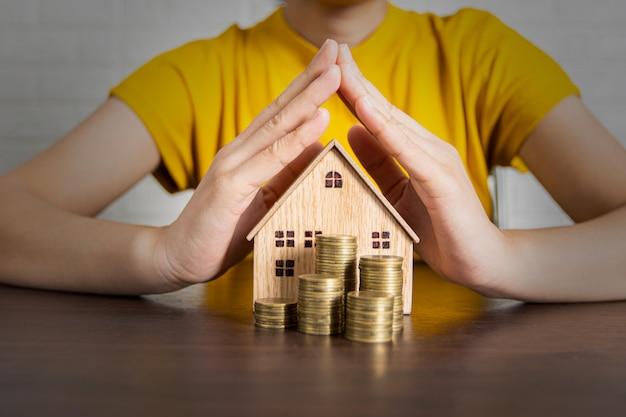 Mãos protegendo moedas e casa de brinquedo