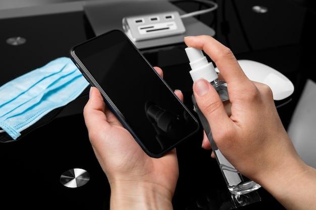 Mãos pulverizando desinfetante em um telefone