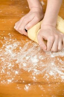 Mãos que amassam a massa de pão