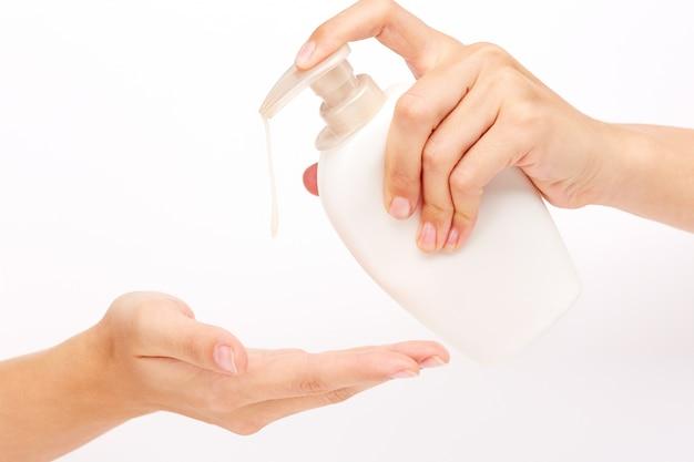 Mãos que aplicam o sabão líquido branco